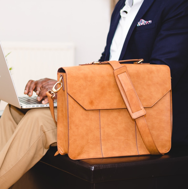 A person sitting beside their leather satchel