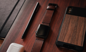 Mobile phone, smartwatch, and pen on a wooden desk
