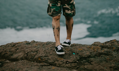 The legs of a hiker standing on top of a mountain, wearing camo shorts and sneakers.