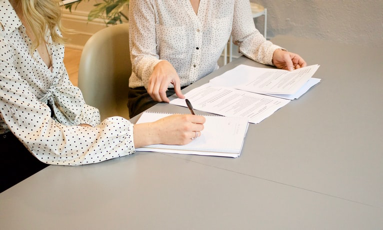 A manager helping a new hire sign onboarding documents